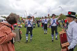 Men traditionally dressed and dancing in a field with two musicians and spectators.