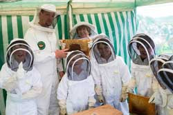 Children with two adults in full protective outfits for collecting honey from bee nests. One child and Deputy Mayor of Hincklkey and Bosworth, Jan Kirby holding a insert from hive with honey
