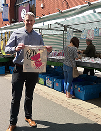 Assistant Town Centre Manager John Coward holding this year's tote bag on Hinckley Market