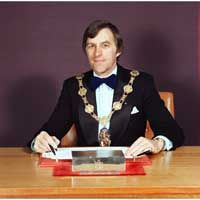 Man sitting at a desk wearing a jacket, shirt, bow tie and a large gold chain with council crest hanging from it. Former mayor, Mike Preston.