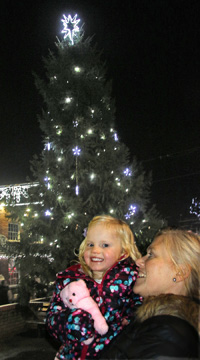 Lady and child in front of Christmas tree with lights and star
