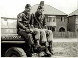 Two male soldiers sitting on a bonnet of a jeep, wearing uniform leather jackets, trousers, boots and caps. Black and White old photo.
