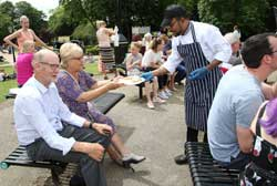 People outside sitting on benches and woman being handed a plate of food by a man in a stripped apron