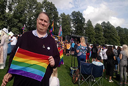 Photo of Mathew Hulbert holding the pride flag