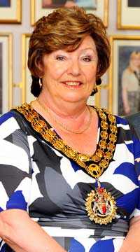 Lady, siting in blue, white, black and grey dress wearing large heavy gold chain with pendant of Hinckley and Bosworth Borough Council's crest, which is the mayors chain.