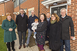 A family and council representatives standing outside new home