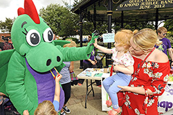 Snappy the Snap Dragon 'high-fiving' a young child at Argents Mead bandstand